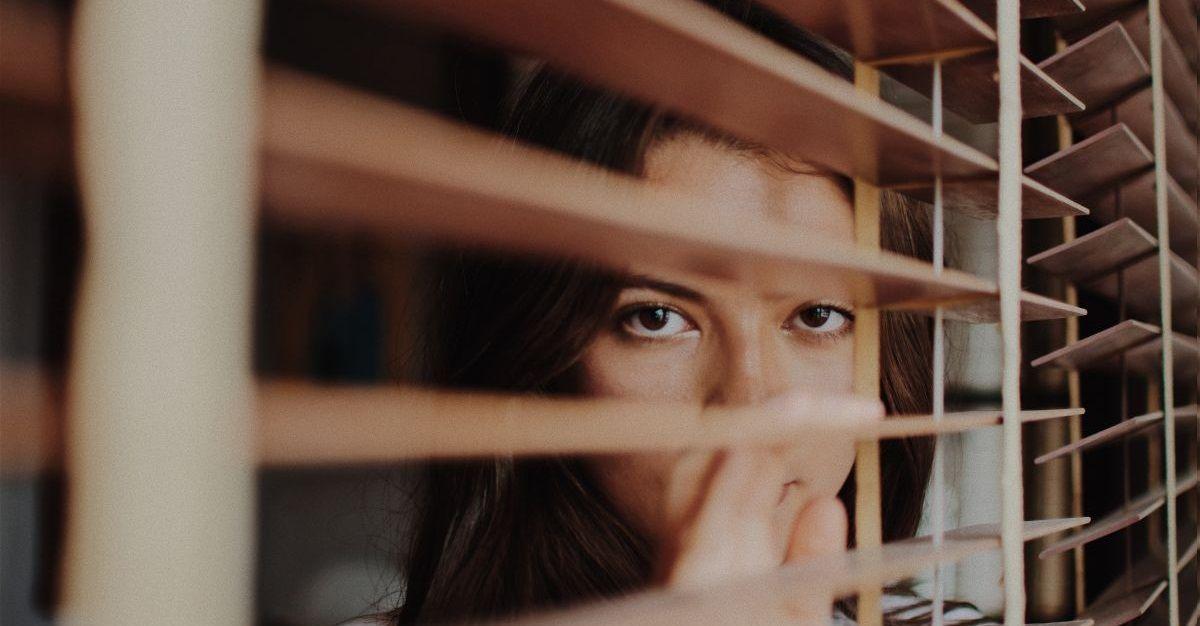 Femme regardant à travers des rideaux